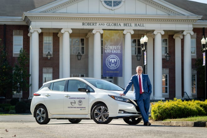 Tennessee Tech President Phil Oldham poses with electric car.