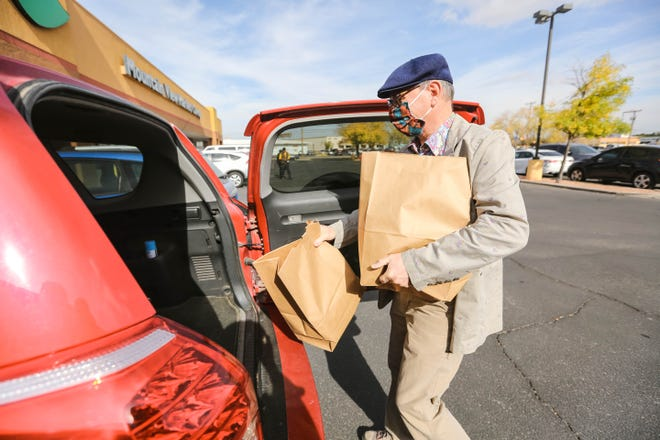 Robert Hull, a 30-year member of Mountain View Market Co+op, puts groceries in his car in Las Cruces on Monday, Nov. 23, 2020.