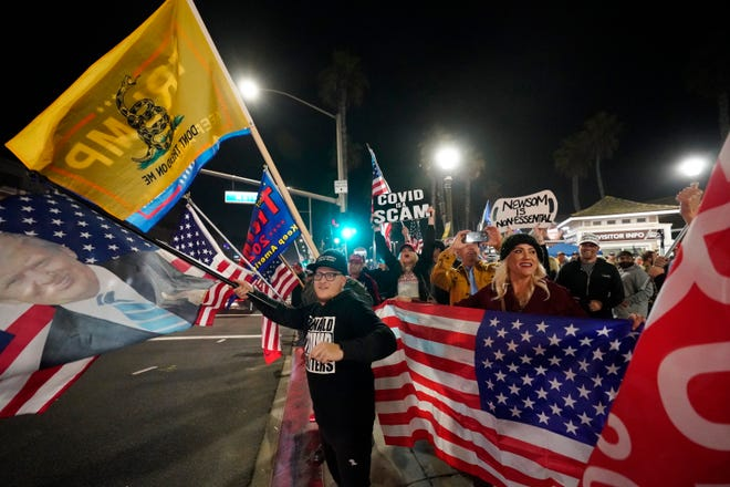 Demonstrators wave flags along Pacific Coast Highway Saturday, Nov. 21, 2020 during a protest against a stay-at-home order amid the COVID-19 pandemic in Huntington Beach, Calif. California health officials are restricting overnight activities starting Saturday night, though there are plenty of exceptions. They're calling it a limited stay-at-home order designed to stem the rapidly spreading coronavirus by discouraging social gatherings.