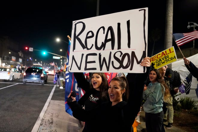 In this file photo, demonstrators shout slogans while carrying a sign calling for a recall on Gov. Gavin Newsom during a protest against a stay-at-home order amid the COVID-19 pandemic in Huntington Beach.