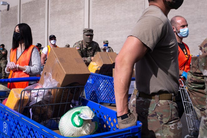 Volunteers and Arizona Army National Guard members wait with loaded carts on Nov. 23, 2020, during the holiday food distribution at St. Mary's Food Bank in Phoenix, Arizona.