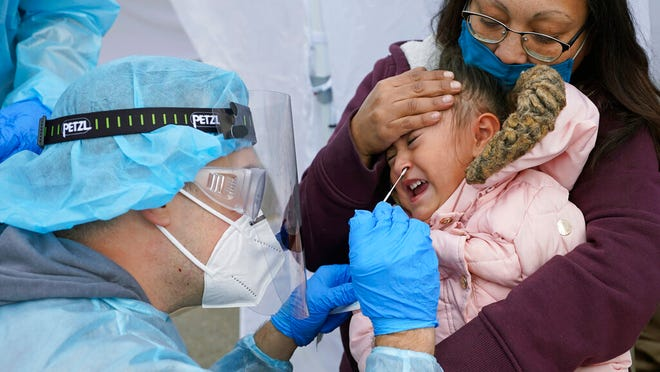 FILE - In this Nov. 10, 2020, file photo, Kim Tapia holds her granddaughter Amariah Lucero, 3, as she's tested at the Utah National Guard's mobile testing site for COVID-19 in Salt Lake City. The U.S. has recorded about 10.3 million confirmed infections, with new cases soaring to all-time highs of well over 120,000 per day over the past week. (AP Photo/Rick Bowmer, File)