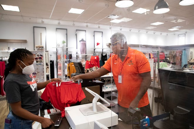 Sole Queen Owner Rory Newkirk rings up Sabrina Bell as she finishes shopping at the store inside Governor's Square Mall Monday, Nov. 23, 2020.