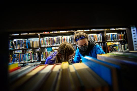 Beatrix Robb, 13, of Brattleboro, Vermont, and her mother, Jen, look for a book at the Brooks Memorial Library, in Brattleboro Nov. 13, 2020.