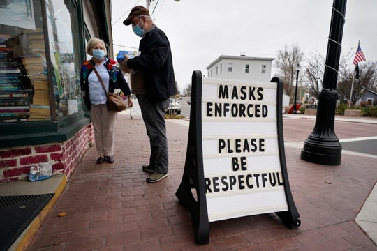 Shoppers comply with the mask regulations to help prevent the spread of the coronavirus at Bridgton Books Nov. 13, 2020, in Bridgton, Maine.