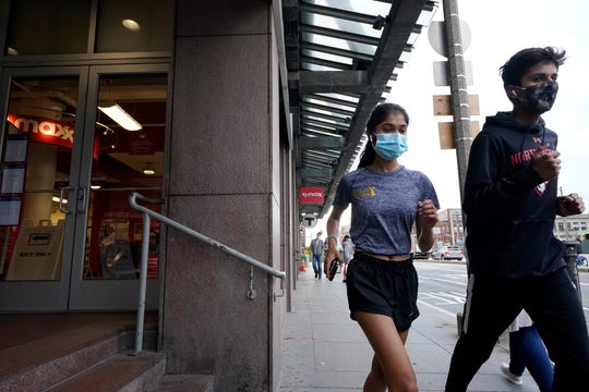 Runners wear masks while jogging along a sidewalk Oct. 27, 2020, in Boston.