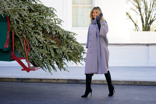 First lady Melania Trump waves as she stands next to the 2020 Official White House Christmas tree as it is presented on the North Portico of the White House, Nov. 23, 2020, in Washington. (AP Photo/Andrew Harnik) ORG XMIT: DCAH406