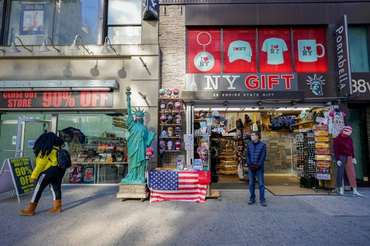 A shopkeeper at a gift shop along 34th Street stands on the sidewalk waiting for customers Nov. 20, 2020, in New York.