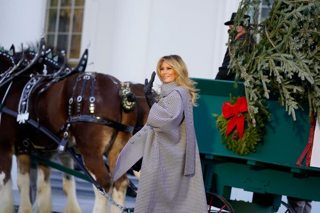 First lady Melania Trump waves as she stands next to the 2020 Official White House Christmas tree on Nov. 23, 2020.