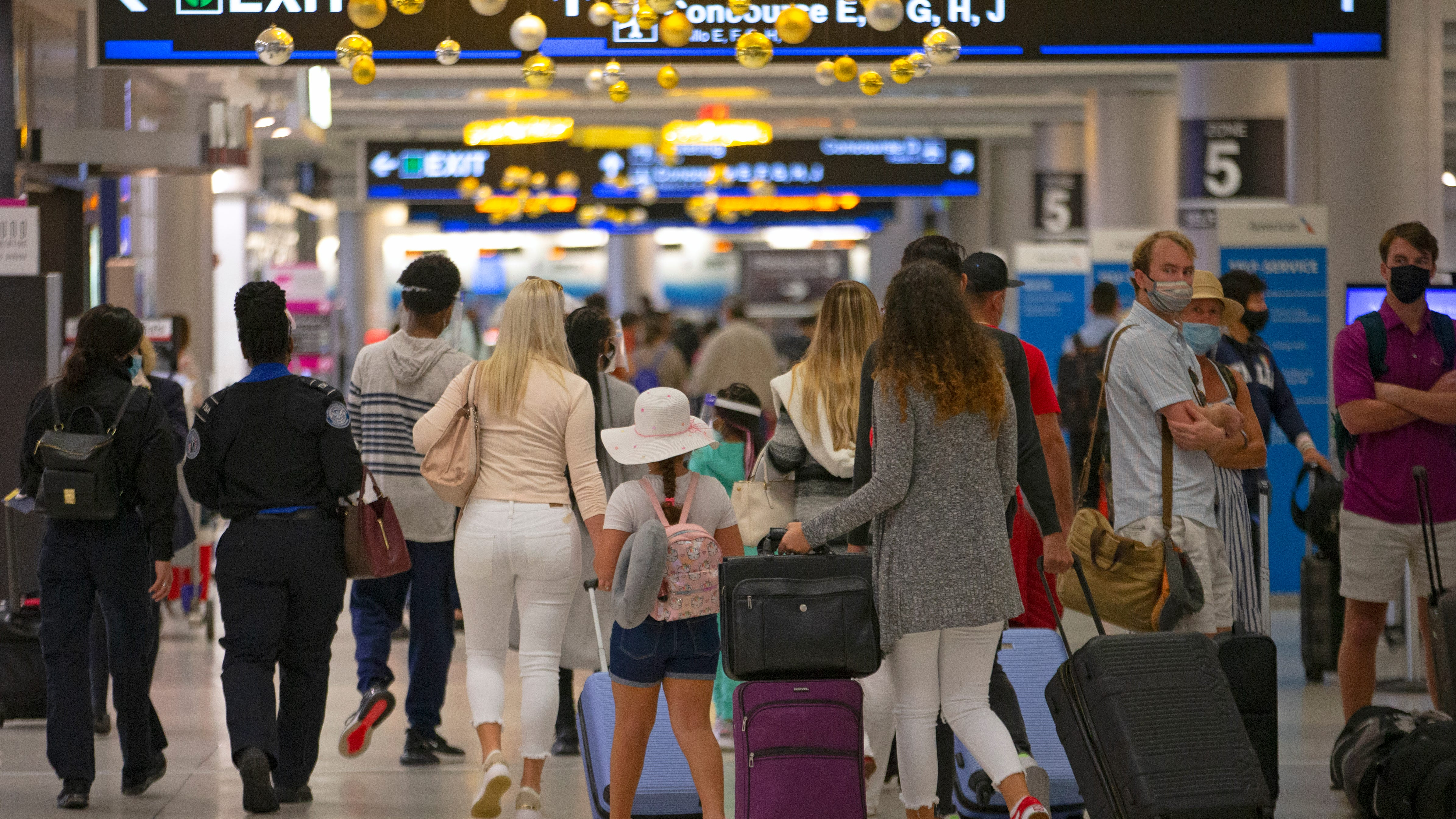 Travelers wearing protective face masks walk through Concourse D at the Miami International Airport on Nov. 22.