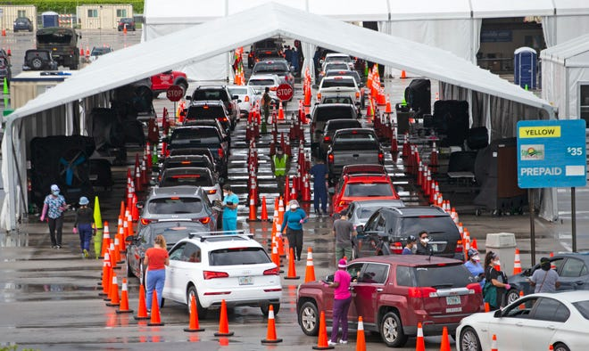 Vehicles line up at a COVID-19 drive-thru testing center on Sunday at Hard Rock Stadium in Miami Gardens, Florida.