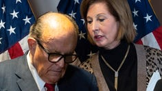 Former Mayor of New York Rudy Giuliani, left, listens to Sidney Powell, both lawyers for President Donald Trump, during a news conference at the Republican National Committee headquarters, Nov. 19, 2020, in Washington.