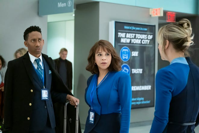 "Flight attendants Shane (Griffin Matthews), left, and Megan (Rosie Perez) suspect their colleague Cassie (Kaley Cuoco) was out with one of their passengers in the hours before he was found dead in his hotel the next day in HBO Max's ""The Flight Attendant."""