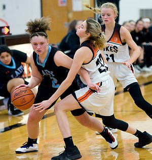 Alliance's Mackenzie Fletcher handles the ball as she is defended by Marlington's Sierra Thompson (22) and Mary Mason in an Eastern Buckeye Conference game in February 2020.