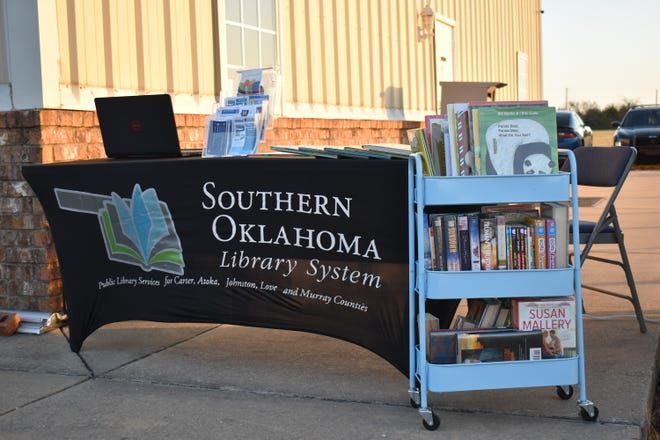A selection of books and an information table sit outside of the Dickson Community Center.