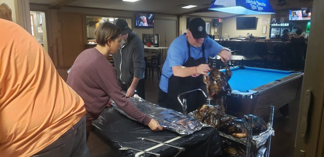 Ardmore Elks wrap smoked turkeys in foil for their meal packages. In total over 660 people including over 150 families were fed during the third annual Feeding Families in Need event.