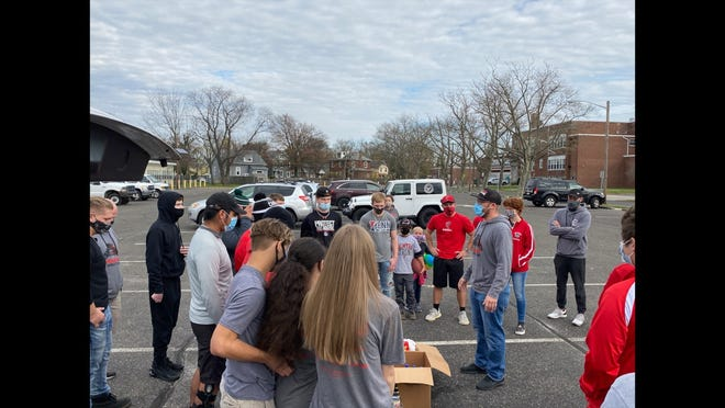Palmyra wrestling coach Zach Stosius (right) talks to members of the Panthers wrestling team at a donation drop off at the high school Friday.