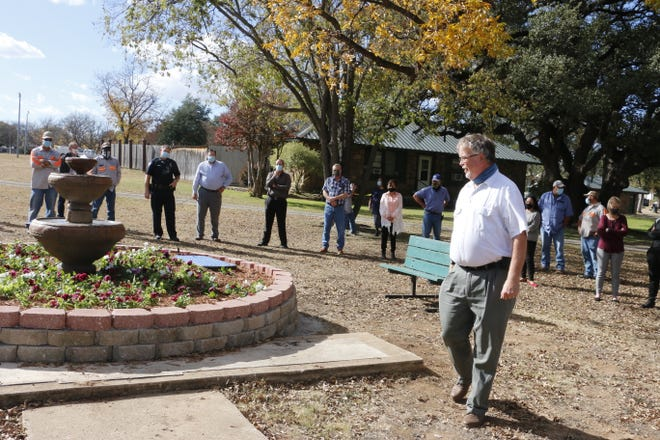 """David Withers' colleagues with the City of Brownwood stand near the """"Fountain of Service"""" as Withers (foreground) looks at the fountain Tuesday at Coggin Park"""