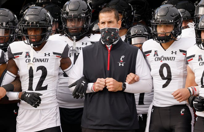 Cincinnati Bearcats head coach Luke Fickell (middle) and quarterback Desmond Ridder (9) and cornerback Ahmad Gardner (12) lead the team onto the field before the game against the UCF Knights at the Bounce House in Orlando, Fla., on Nov. 21, 2020.