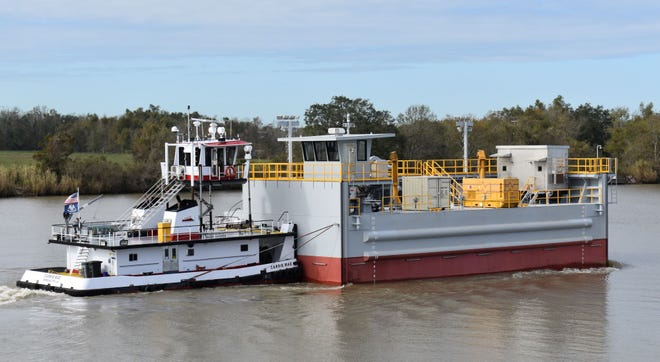 A boat pushes a floodgate built by Lockport-based Bollinger Shipyards to its site along Bayou Teche in in St. Mary Parish.
