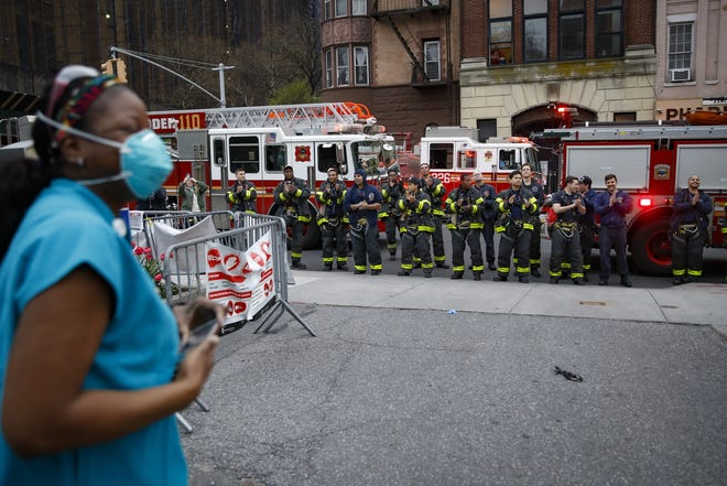In this April 14, 2020, file photo FDNY firefighters gather to applaud medical workers as attending physician Mollie Williams, left, wears personal protective equipment due to COVID-19 concerns outside Brooklyn Hospital Center in New York. Essential workers are lauded for their service and hailed as everyday heroes.