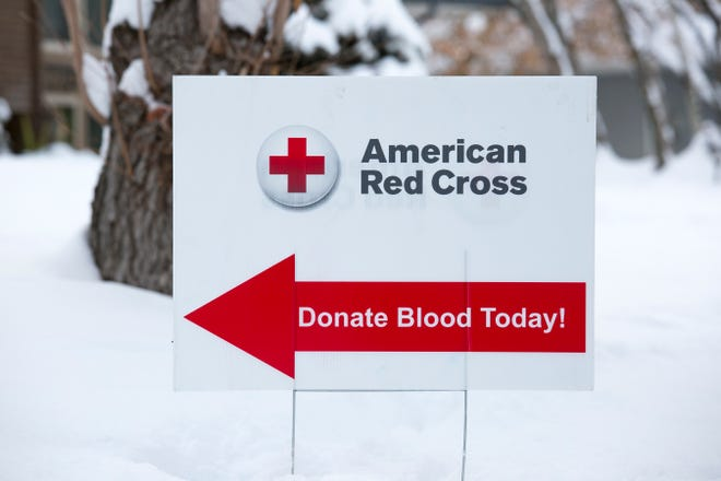 A sign advertises for a blood drive in winter weather.