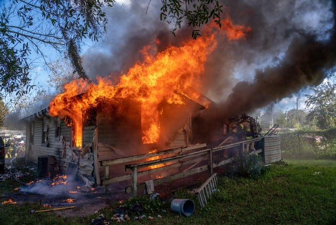 Flames erupt from an Acorn Street home as Jacksonville firefighters try to get inside to search for a possible victim. No one was inside, but four firefighters were injured, the fire department said.