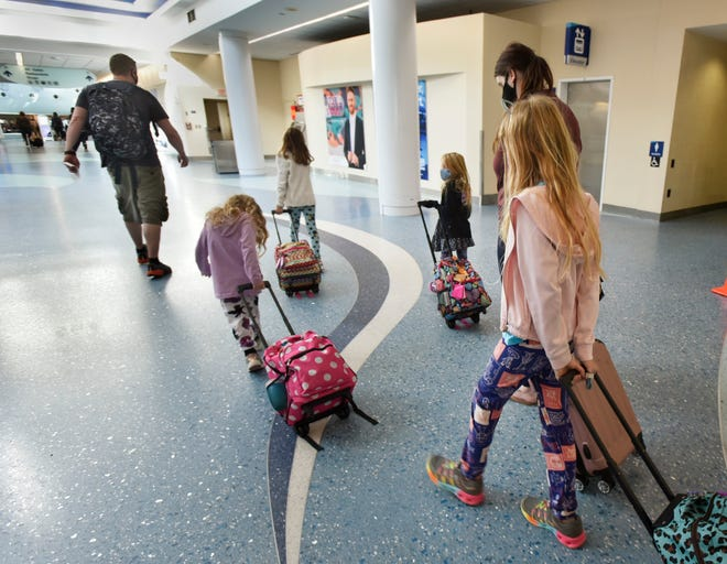 Derek Austin (left) and his family, all masked, head to their flight Tuesday at Jacksonville International Airport.