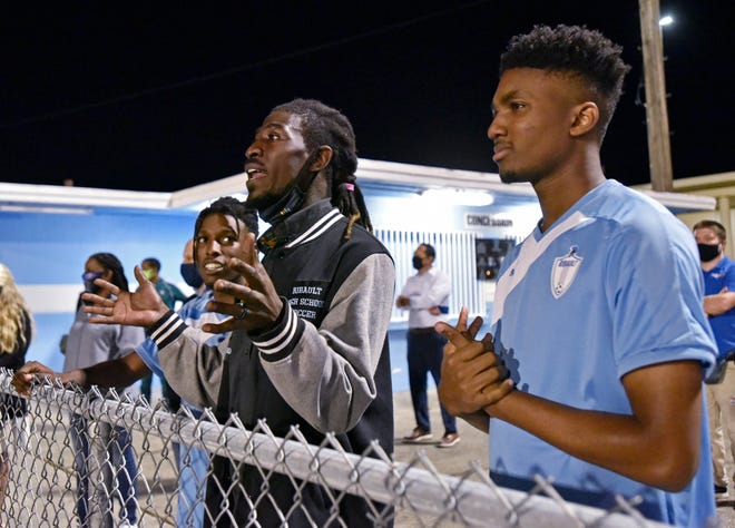 Ribault boys soccer coach Trey Brown (center) watches a girls game with his players De'Audrie Smith (left) and Zavion Houston at the school on Monday. The boys and girls teams were given new uniforms Monday, the final stage of a community effort to give the cash-strapped program a new lease on life.