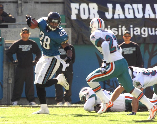 Jacksonville Jaguars running back Fred Taylor (28) turns the corner on Miami Dolphons defender Patrick Surtain (23) and heads down the sidelines on a 90-yard touchdown run during the first quarter of their AFC divisional playoff game Saturday, Jan. 15, 2000, in Jacksonville, Fla.  (AP Photo/Mark Duncan)
