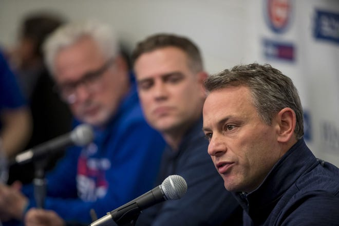 Cubs president Jed Hoyer, who was the team's GM at the time, speaks at spring training on Feb. 12, 2019. Ex-Cubs manager Joe Maddon, and former team president Theo Epstein, both in the background, listen to Hoyer's remarks.