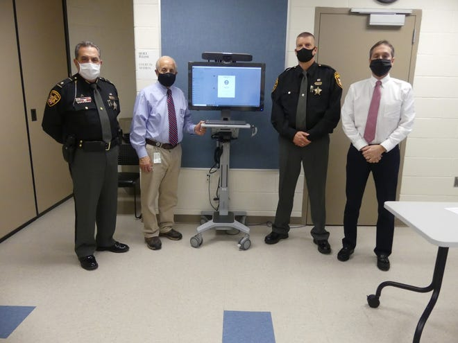 Stark County Sheriff George Maier (left), Massillon Judge Edward Elum, Deputy Tim Miller and Judge Joel Fichter are pictured with newly acquired equipment that assists with inmate court proceedings.