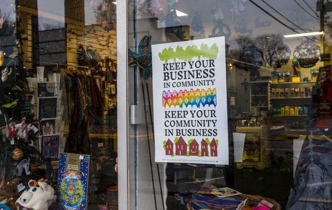 A sign on the window at Global Village in Peoria Heights encourages local shopping.
