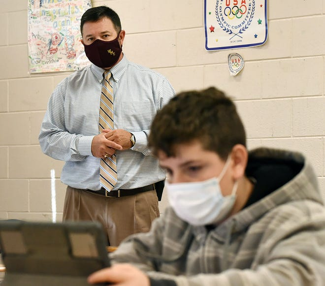 Principal Patrick Phillippe visits a class at Woodington Middle School, where stronger relationships between students, teachers and parents has driven a sharp decrease in out-of-school suspensions over the past five years, a trend mirrored by schools across LCPS.