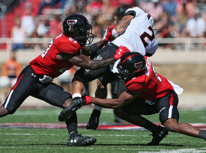 Texas Tech cornerbacks DaMarcus Fields, left, and Zech McPhearson, right, tackle Oklahoma State wide receiver Tylan Wallace (2) during the Red Raiders' 45-35 victory last year in Lubbock. The two teams meet again at 11 a.m. Saturday in Stillwater, Oklahoma.