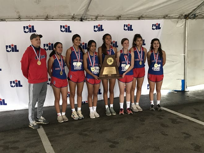 The Sundown girls cross country team and Roughettes coach Paul Darden (left) pose with the Class 2A state cross country after winning the meet on Tuesday, Nov. 24, 2020 at Old Settler's Park in Round Rock.