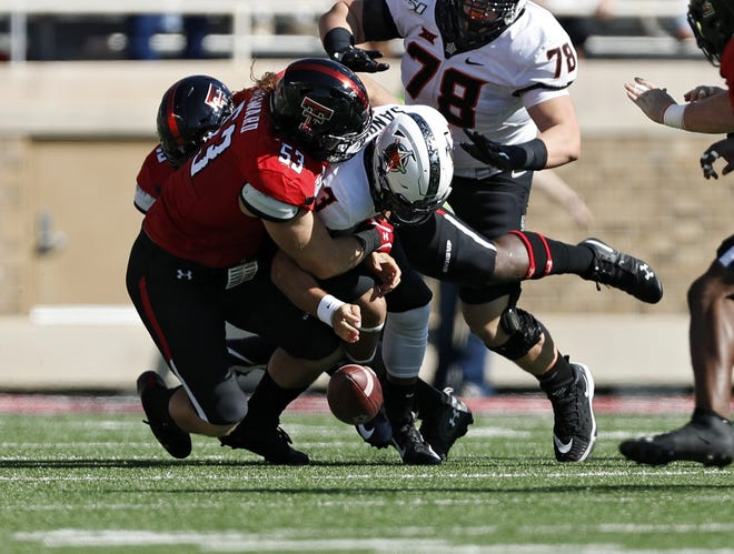 Defensive end Eli Howard (53) and the Texas Tech defense made it a miserable day for Oklahoma State quarterback Spencer Sanders last year at Jones AT&T Stadium. The Red Raiders sacked Sanders seven times, and the Cowboys' quarterback threw three interceptions and lost a fumble, above. The two teams meet again Saturday in Stillwater, Oklahoma.