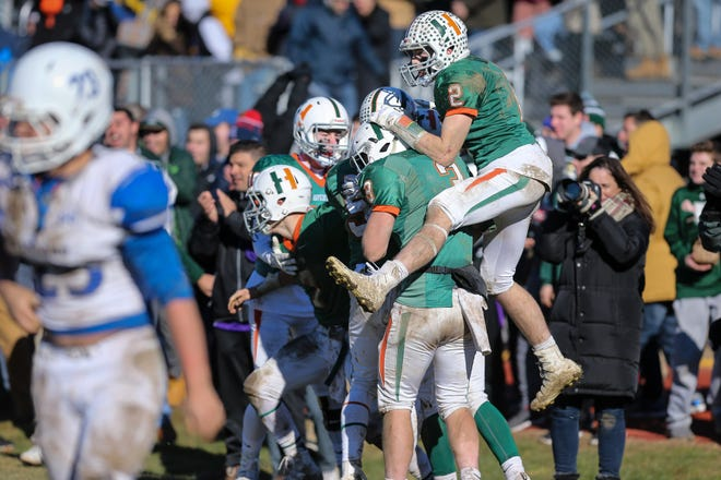 Former Hopkinton football player Will Abbott (top right) leaps onto teammates after a win over Ashland on Thanksgiving at Hopkinton High School on Nov. 23, 2017.  The two teams didn't get to play this Thanksgiving due to the ongoing COVID-19 pandemic.