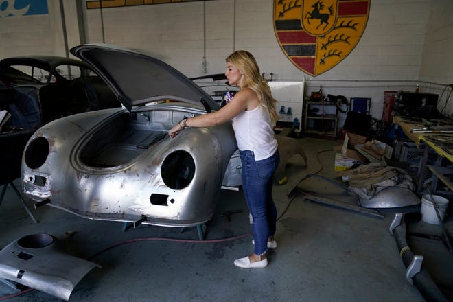 Laurina Esposito, co-owner of Espo Restoration, which specializes in restoring Porsches, inspects a frame at her shop in the North Hollywood section of Los Angeles. Esposito and her business partner were diagnosed with coronavirus in early September. She was very ill for three weeks and did as much work as she could on her laptop in bed, but at times was too exhausted. (AP Photo/Marcio Jose Sanchez)