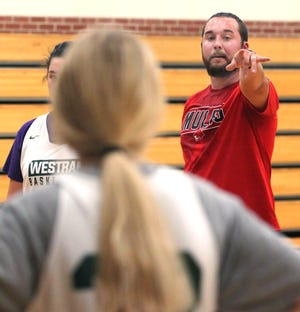 Westran High School first year varsity girls basketball coach Alex Thomas points as he provides instruction to his girls during practice.