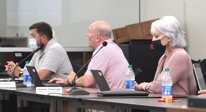 Moberly school board members Heather Cleavinger, from right, Dan Wilcox and Scott Head study a report while listening to a presentation during a monthly business meeting.