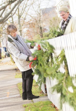 Jean and Mike Walsh decorate the fence in front of their Harrison Avenue home in 2012.