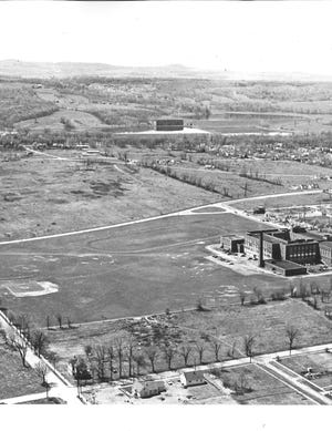 Thomas R. Proctor High School sure looked lonely out there in 1953. No Mohawk Valley Community College and Columbus School as neighbors. No expansion buildings surrounding it. No tennis courts or football stadiums. Just a little 17-year-old high school – it opened on September 6, 1936 – with 200 rooms of various sizes and shapes to accommodate 2,200 students. Its cafeteria was one of Utica's largest eating places. It seated 750 and had a serving counter 50 feet long. This photo was taken looking southwest toward Armory Drive and the reservoirs on Pleasant Street. The city's large ice house can be seen in the top center of the photo.