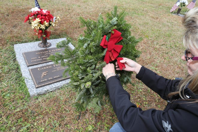 In this 2017 file photo, Carrie Priebe Daffron lays a Christmas wreath on the gravesite of her husband, Devlin, who was a Navy veteran. This year's Wreaths Across America ceremony will be held Dec. 19 at Highland Memorial Park in Ocala.