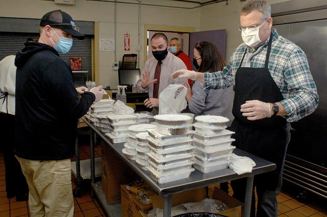 Marshwood High School Principal Robert Scully, left, District Financial Manager Ryan Cormier and District Curriculum Director Heidi Hersey center, and Superintendent John Caverly, right, stand before piles of packages to be assembled into free Thanksgiving dinners for Marshwood families Tuesday at Marshwood Middle School.