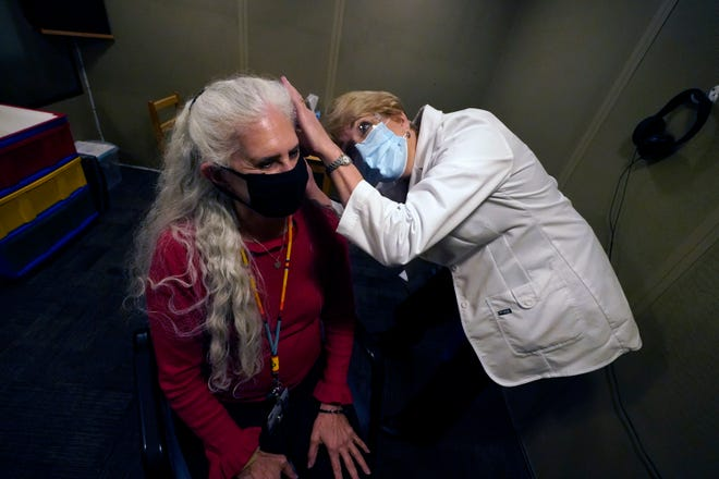 Andrea Gohmert, right, director of the hearing clinic at the University of Texas at Dallas Callier Center for Communication Disorders, prepares Lynne Perler for a hearing test during a demonstration at the Callier Center in Dallas. Hearing specialists across the U.S. are seeing an uptick in visits from people who only realized how much they relied on lip reading and facial expressions when people started wearing masks because of the coronavirus pandemic.