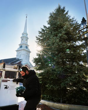 """Steve Burns, an arborist for the City of Portsmouth, carries a ball of lights to decorate the holiday tree  in Market Square last December. The city will hang decorated shamrocks on it for St. Patrick's Day to create a """"Tree of Luck."""""""