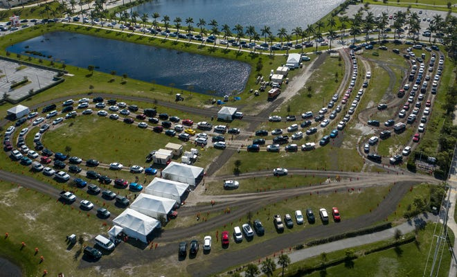 People line up Tuesday to be tested for COVID-19 at a testing site at FITTEAM Ballpark of the Palm Beaches in West Palm Beach.