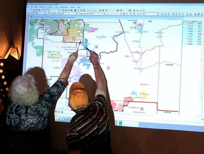 Two people discuss a detail of a district map at a 2011 meeting of Arizona's nonpartisan redistricting commission.