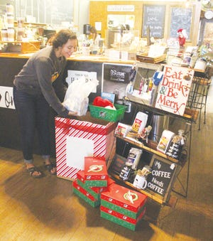Kierra Messick places toy and gift donations for Operation Christmas Child into a collection box set up by Liberty Middle School student Sydney Riley at N'Cahoots Coffee &Shoppe on Saturday. More than 1,100 shoe boxes were packed for needy children by Pratt community members.